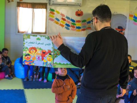 A man shown from behind is showing a book to young children in a classroom