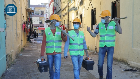 Three young men walking in Beirut after the Blast, wearing construction helmet and holding shovels