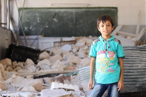 A young boy is standing in a class that was destroyed