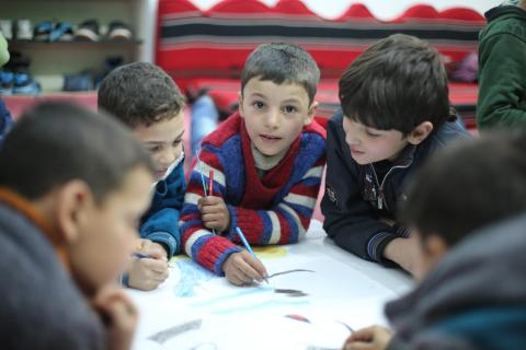 Young boys attend a basement school in besieged East Ghouta and are drawing on a table