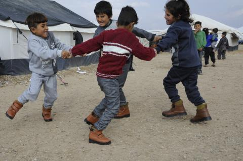 Four children dancing in circle and holding eachothers hand outside, in a camp