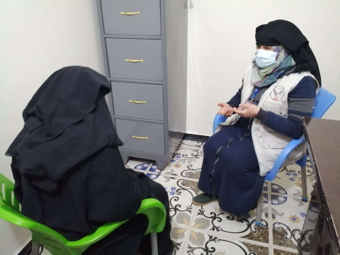 A female doctor is listening to her patient, they are both sitting on chairs