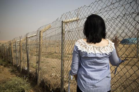 A young girl seen from the back facing a fence