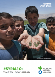 Four children are outside, one of them is showing seeds in his hands