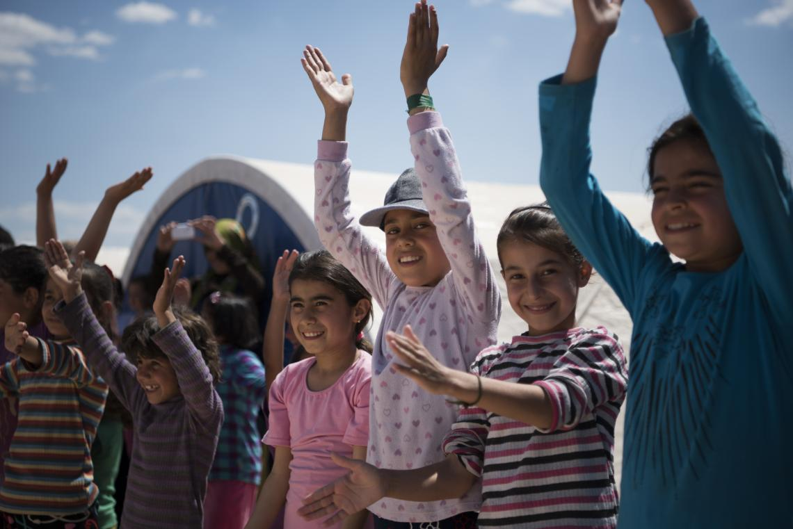 A group of children is waiving outside a camp