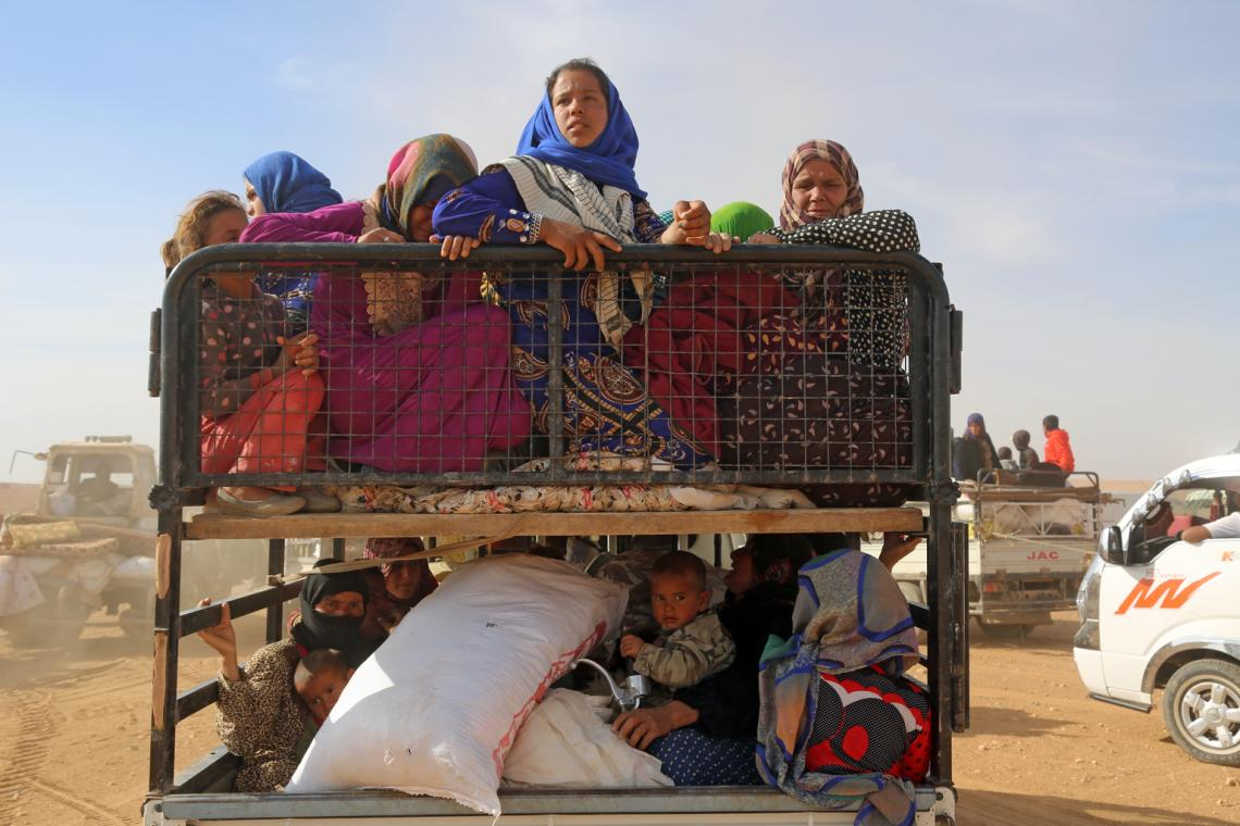 A group of adults and children carrying their belongings on a truck